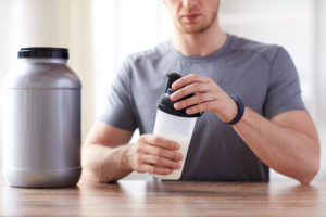 sport, fitness, healthy lifestyle and people concept - close up of man in fitness bracelet with jar and bottle preparing protein shake